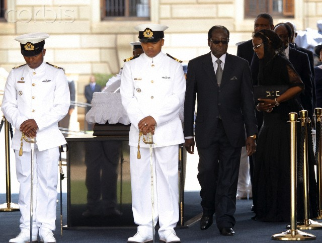 Zimbabwe's President Robert Mugabe and his wife Grace pay their respects at the coffin of former South African President Nelson Mandela as he lies in state at the Union Buildings in Pretoria