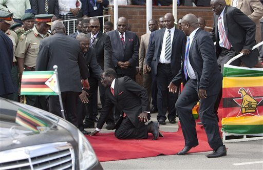 Zimbabwean President Robert Mugabe, center, falls after addressing supporters upon his return from an African Union meeting in Ethiopia, Wednesday, Feb. 4, 201 n