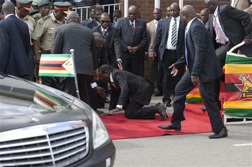 Zimbabwean President Robert Mugabe, center, falls after addressing supporters upon his return from an African Union meeting in Ethiopia, Wednesday, Feb. 4, 201