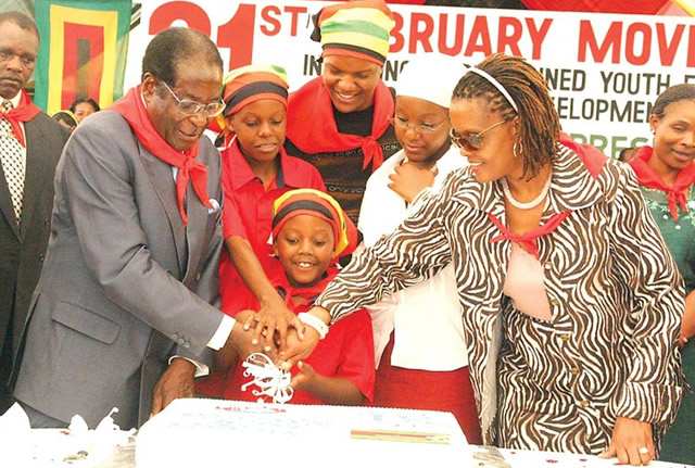 2102-1-1-PRESIDENT-MUGABE-CUTTING-HIS-BIRTHDAY-HELPEDBY-GRACE-MUGABE-AND-THIER-CHILSDREN-LOOKS-ON-21-02-13