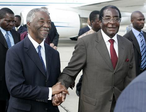 Zimbabwe President Robert Mugabe (R) walks with South Africa President Thabo Mbeki on his arrival in the capital Harare.